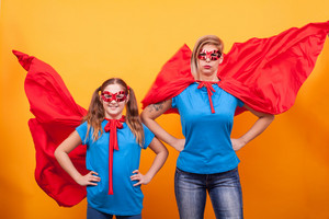 Mother and daughter dressed like superheros with their red capes in the air over yellow backgtound. Mother and daughter adventure. Happy childhood.