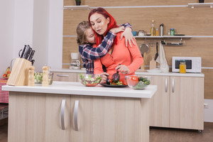 Mother and daughter having a sweet moment while cooking. Strong conection.