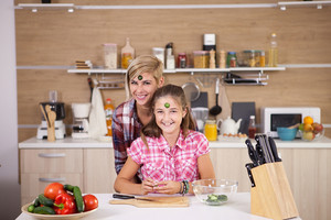 Mother and daughter joking around while they cook together. Happy kid.