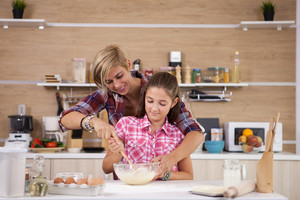 Mother and daughter making cookies in home kitchen. Parents care.