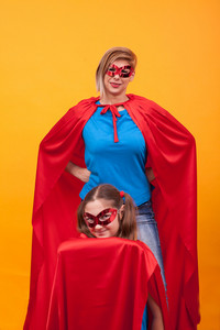 Mother and daughter playing together dressed like superheros. Little game. Happy Kid. Happy childhood. Mother and daughter connection.