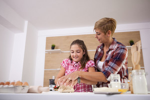 Mother and daughter prepare dough baking apple cake happy together. Good food.
