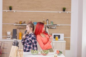 Mother and daughter singing on kitchen intruments. Funny moment.