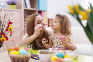 Mother and her baby have fun while painting easter eggs