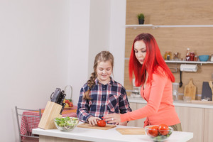 Mother chosing the right knifes for the job. Teaching her daughter to cook,.