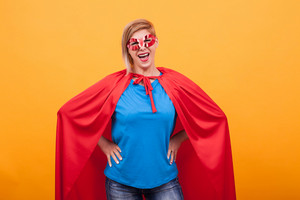 Mother dressed like superheros laughing at the camera over yellow background. Super powers. Red mask. Red cape.