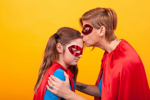 Mother in superman costume kissing her little girl forehead over yellow background. Red cape. Red mask. Mother's love.