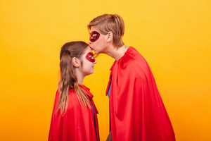 Mother in superman costume kissing his little girl forehead over yellow background. Red cape. Red mask. Mother's love.