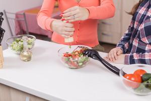 Mother pouring salt over green salad in kitchen. Secret ingredient.