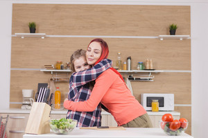 Mother showing affection to her daughter while cooking brunch.
