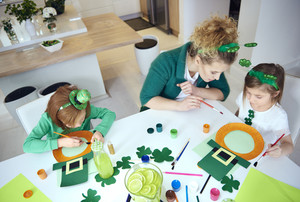 Mother with children preparing decorations for Saint Patrick's Day