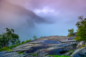 Mountain landscape in early morning with cloudy sky. Composition of nature with bench, Geirangerfjord, Norway