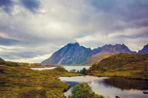 Mountain landscape. Rocky shore of mountain lake in rainy autumn morning. Beautiful nature Norway.