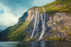 Mountain landscape with cloudy sky. Beautiful nature of Geirangerfjord, Norway, Seven Sisters Waterfall