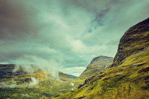 Mountain misty autumn landscape with dramatic cloudy sky Norway