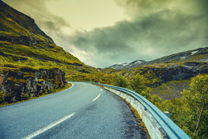 Mountain road in Norway with dramatic cloudy sky