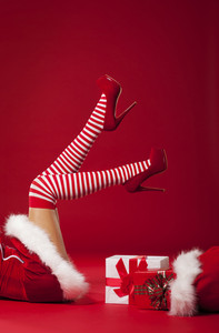 Mrs santa claus legs in striped stockings with christmas gifts