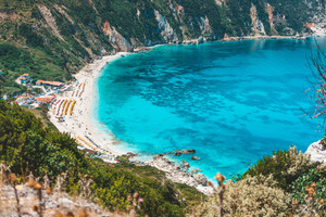 Myrtos beach with azure blue sea water in the bay. Favorite tourist destination to visit in summer on Kefalonia island, Greece, Europe