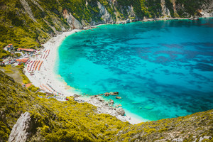 Myrtos beach with azure blue sea water in the bay. Favorite tourist visiting destination place at summer on Kefalonia island, Greece, Europe