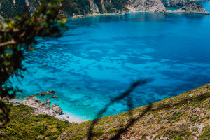 Myrtos beach with azure blue sea water in the bay with dark pattern on bottom. Favorite tourist visiting destination location at summer on Kefalonia island, Greece, Europe