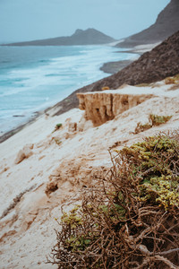 Mysterious landscape of sand dunes and black volcanic mountains along coastline. Baia Das Gatas. North of Calhau, Sao Vicente Island Cape Verde