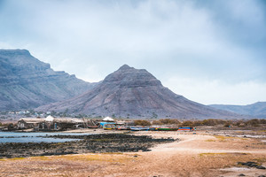 Mysterious landscape of sandy coastline with fisher village and black volcanic mountains in background. Baia Das Gatas. North of Calhau, Sao Vicente Island Cape Verde