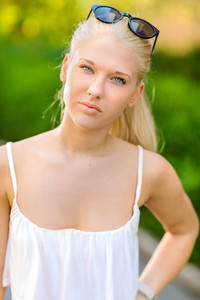Natural blonde teen girl standing in the street in the sun