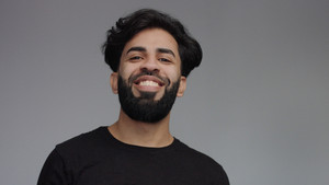 natural laugnig man in studio on grey