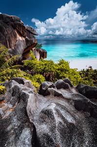 Natural viewpoint to beautiful impressive Grand Anse beach on La Digue island in Seychelles. Amazing white clouds above ocean horizon