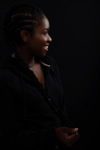 Natural woman with dark skin laughing and wearing black hoodie