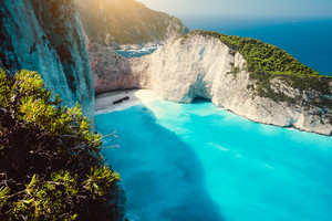 Navagio beach. Shipwreck on beach in morning light. Turquoise water and limestone rocks surrounding. Famous landmark visiting location on Zakynthos island, Greece