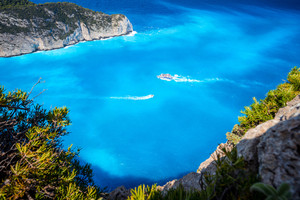 Navagio beach, Zakynthos, Greece. Tourist trip boats visiting and leaving Shipwreck bay with turquoise water beach surrounded by bizarre cliff rocks. Famous landmark location