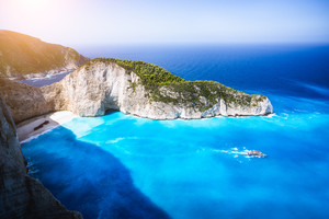 Navagio beach, Zakynthos island, Greece. Tourist trip boat leaving Shipwreck bay with deep turquoise water and white sand beach surrounded by bizarre cliff rocks. Famous landmark location