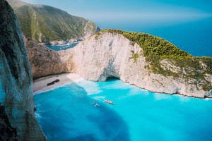 Navagio beach, Zakynthos island, Greece. Two tourist boats leaving Shipwreck bay with turquoise water and white sand beach. Famous landmark location in Greece