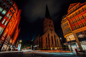 Night photography of Hamburg on the crossroad. View of St. Petri church and traditional red brick buildings. Long exposure. Car light trails. Hamburg, Germany