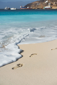 Ocean waves rolling to the foot prints on the tropical beach with azure water