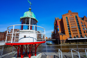 Old beacon or small lighthouse near river channel in Hamburg Hafencity