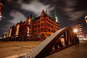 Old Speicherstadt in Hamburg illuminated at night. Arch bridge and historical buildings. Warehouse District -Speicherstadt Landmark of HafenCity quarter