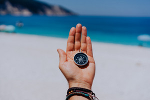 One open stretched hand palm with black metal compass on the sandy beach. Find your wish goal way concept. Blue sea in background. Point of view pov