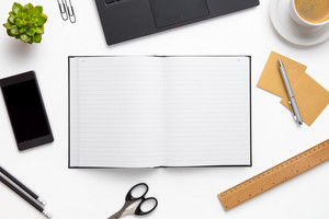 Open Diary Surrounded With Office Supplies On White Desk