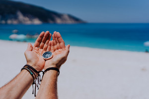 Open hand palms holding metal compass against sandy beach and blue sea. Searching your way concept. Point of view pov