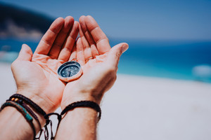 Open hand palms with metal compass on the sandy beach. Searching your way concept. Blue sea in background. Point of view pov