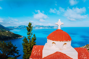 Orange colored Hellenic shrine Proskinitari on the cliff edge with defocused sea and cloudscape view in the background