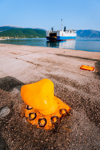 Orange Mooring Bollard and big ferry boat with passengers and cars arrives beautiful greek island. Summer vacation