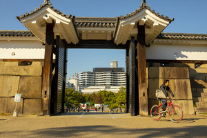 osaka japan - november7,2018 : unidentified people riding bicycle passing through entry door to osaka castle one of most popular traveling destination in osaka city japan