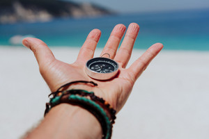 Outstretched hand holding black metal compass against white sandy beach and blue sea. Find your way or goal concept. Point of view pov