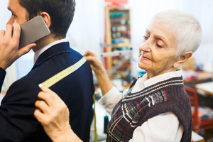 Owner of tailoring-shop measuring back width of man jacket