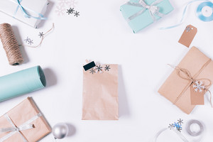 Package with gift, Christmas decorations, snowflakes and boxes on a white table top view