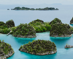 Painemo, Group of small island in shallow blue lagoon water, Raja Ampat, West Papua, Indonesia