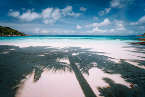 Palm tree shadow on tropical white sand beach wirh blue ocean clouds